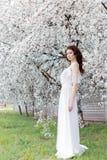 有柔和的眼睛构成充分的嘴唇的美丽的逗人喜爱的甜性感的女孩新娘在白光礼服在温暖的s的繁茂花园里走 库存照片