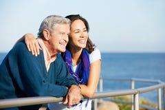 有查看海运的成人女儿的老人 免版税库存图片