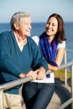 有查看海运的成人女儿的老人 免版税库存照片