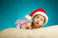 有查寻圣诞老人的帽子的小逗人喜爱的婴孩 免版税库存图片