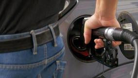 有柴油的人填装的汽车 供以人员` s手使用加油泵用燃料填满他的汽车 股票录像