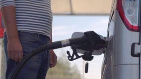 有柴油的人填装的汽车 在汽车柴油坦克和换装燃料插入的燃料喷嘴 影视素材