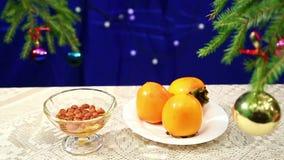 有柿子的板材和坚果用蜂蜜在新年` s背景的桌上与一棵装饰的圣诞树和牧民 股票录像