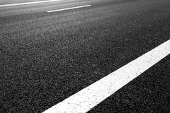 有标号的柏油路排行白色条纹 免版税库存照片