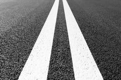 有标号的柏油路排行白色条纹 免版税库存图片