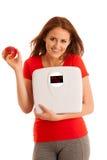 有标度的妇女满意对她的重量被隔绝在白色backg 免版税库存图片