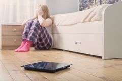 有标度的少年女孩在地板上 免版税图库摄影