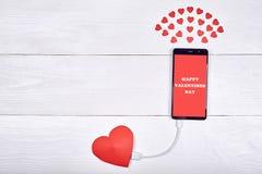 有标志愉快情人节充电的流动巧妙的电话 库存图片