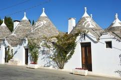 有标志的在屋顶,阿尔贝罗贝洛,意大利两个传统trulli房子 免版税库存照片