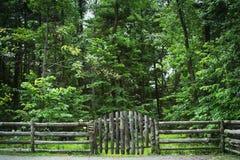 有标志的日志篱芭在森林附近 库存图片
