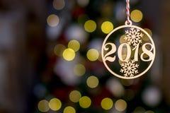 有标志2018年背景边界金黄圣诞树装饰品的木圣诞节玩具和在抽象defocu的假日装饰 免版税图库摄影