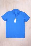 有标签的正面图蓝色球衣在木背景 库存照片