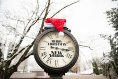 有标题的圣诞快乐纽约葡萄酒时钟和在他们的圣诞老人帽子室外在冬天 免版税库存照片