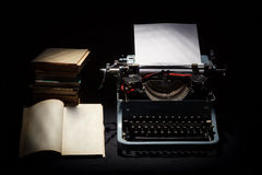有栈的减速火箭的打字机书和一个开张了书 免版税库存图片