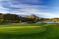 有树、蓝天和山的高尔夫球场 免版税库存图片
