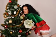 有树和礼物的圣诞节女孩,穿戴在圣诞老人服装 免版税库存图片