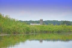 有树和谷仓的反射的湖 库存照片