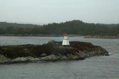 有树木丛生的海岸线的遥远的海岛灯塔在背景中 免版税库存图片