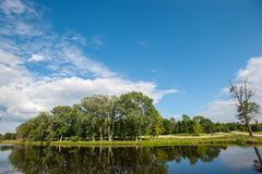 有树的美丽的寂静的湖在天际和白色松的云彩在天空 在村庄的平安的夏日 大绿色 库存照片