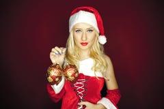 有树装饰品的性感的圣诞节女孩在红色背景 免版税库存照片
