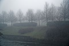 有树雾剪影的,有薄雾的walkside,有雾的地方神秘的步行道路 免版税库存图片