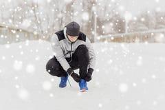 有栓体育鞋子的耳机的人在冬天 图库摄影