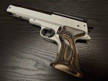 有核桃木夹子的手枪黑表面上 免版税图库摄影