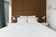 有核桃木铣板的豪华主卧室在床后 库存照片