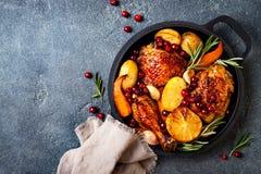 有根菜类、柠檬、大蒜、蔓越桔和迷迭香的烤鸡腿在平底锅 库存图片