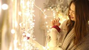 有格子花呢披肩的在她的手微笑和接触电灯泡诗歌选的年轻女人和圣诞老人项目 股票录像
