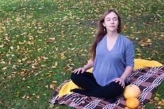 有格子花呢披肩的怀孕的瑜伽妇女和南瓜画象在秋天在草,呼吸,舒展,静止停放 室外,森林 免版税库存照片