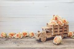 有桃子玫瑰的木玩具卡车在白色的后面开花 免版税库存照片