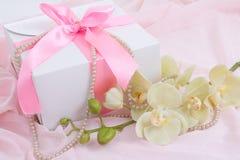 有桃红色丝带、兰花和珍珠项链的礼物盒 免版税库存照片