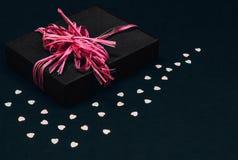 有桃红色丝带弓的黑礼物盒在黑背景洒与心形的五彩纸屑 复制空间 免版税库存图片