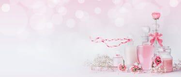 有桃红色丝带的各种各样的化妆站立在与bokeh,正面图,横幅的白色桃红色背景的玻璃瓶和花或 免版税图库摄影