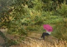 有桃红色伞的女孩 免版税图库摄影