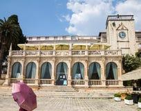 有桃红色伞的妇女在石凉廊前面在赫瓦尔岛,克罗地亚 库存图片