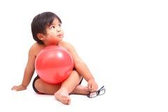 有桃红色健身球的男孩在白色背景 库存照片