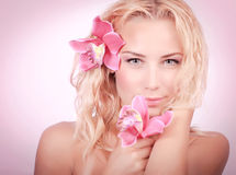 有桃红色兰花的白肤金发的妇女 免版税库存图片