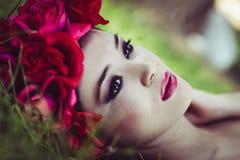 有桃红色和红色花的年轻美丽的日本妇女 免版税图库摄影