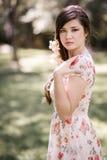 有桃红色和红色花的年轻美丽的日本妇女 免版税库存图片