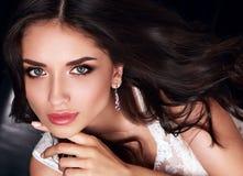 有桃红色唇膏和长的卷发的po美丽的构成妇女 库存图片