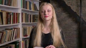 有桃红色唇膏的年轻美丽的白肤金发的女孩是阅读书,观看在照相机,微笑,背景的图书馆 股票录像