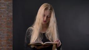 有桃红色唇膏的年轻逗人喜爱的白肤金发的女孩是阅读书,观看在照相机,微笑,灰色背景 影视素材