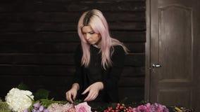 有桃红色头发的一个迷人的卖花人整理在桌上的花,为未来花的布置选择他们 股票录像