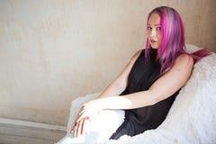 有桃红色头发的女孩在一把椅子坐在一个绝尘室 图库摄影