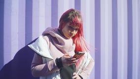 有桃红色头发的独立年轻女人使用在紫色容器背景的智能手机 t 股票视频
