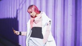有桃红色头发的独立年轻女人使用在紫色容器背景的智能手机 t 股票录像