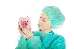 有桃红色存钱罐的女性医生 免版税库存图片