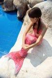 有桃红色尾巴的美人鱼女孩在游泳池边的岩石 免版税库存图片